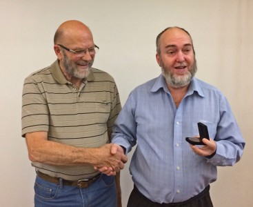 Neil (left) presents the Medal to Richard (right).